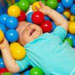 Bébé qui s'amuse et rigole dans des balles multicolores à la crèche