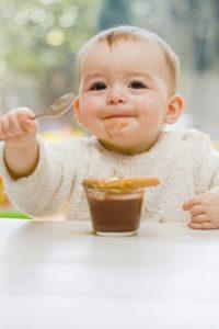 Bébé essaie de manger seul avec une cullière