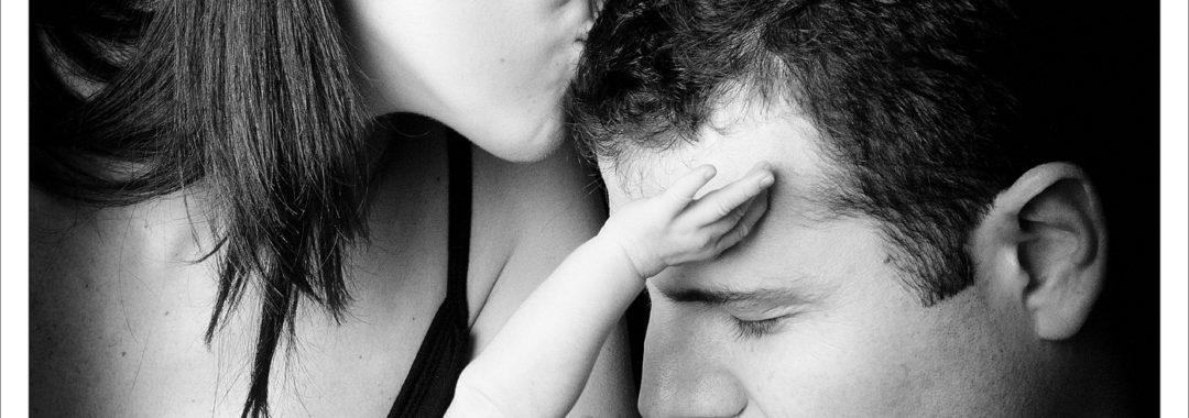 Photo en noir et blanc d'une chaine de bisous entre bébé et ses parents