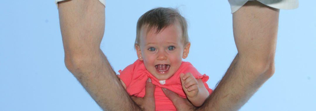 Photo souvenir de bébé dans les bras de son père en contre plongée
